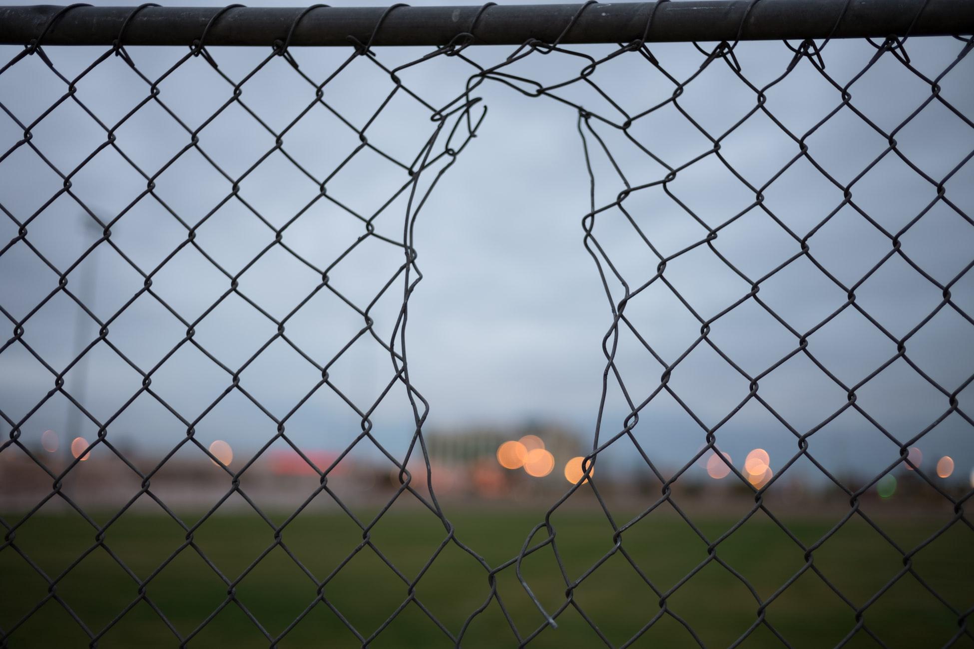 A broken chain link fence creates security vulnerabilities